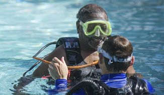 Veteran Earl Williams laughs in a pool while scuba diving in Snowmass Village, Colo., on April 2, 2018 for the National Disabled Veterans Winter Sports Clinic.  (Anna Stonehouse/The Aspen Times via AP)