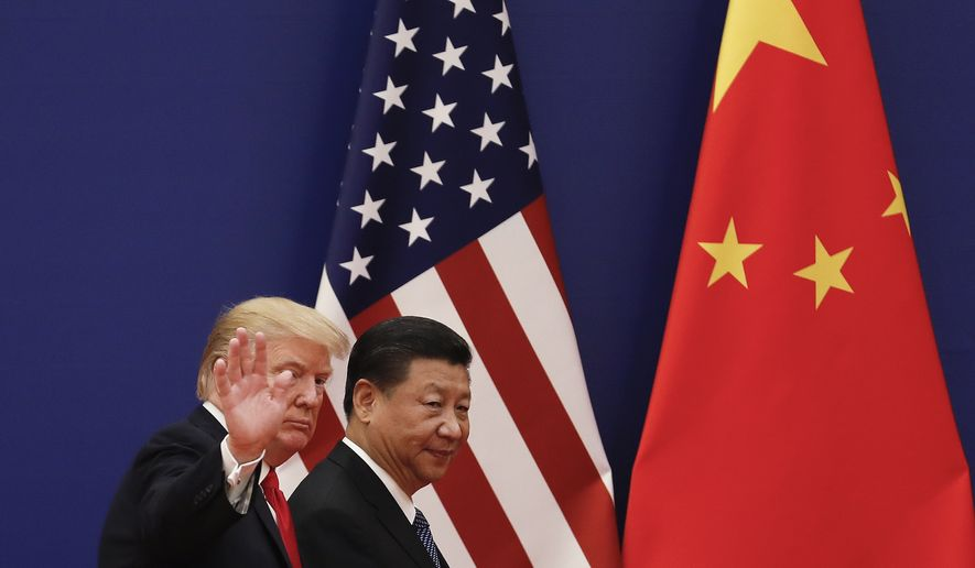 U.S. President Donald Trump waves next to Chinese President Xi Jinping after attending a business event at the Great Hall of the People in Beijing, Thursday, Nov. 9, 2017. Trump is on a five-country trip through Asia traveling to Japan, South Korea, China, Vietnam and the Philippines. (AP Photo/Andy Wong) **FILE**