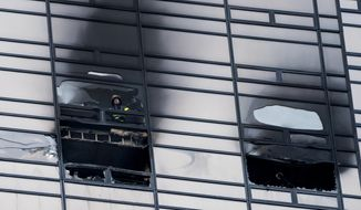 A firefighter looks out from the window of a damaged apartment in Trump Tower in New York on Saturday, April 7, 2018. The New York Fire Department says the blaze broke out on the 50th floor shortly before 6 p.m. Saturday. (AP Photo/Craig Ruttle)