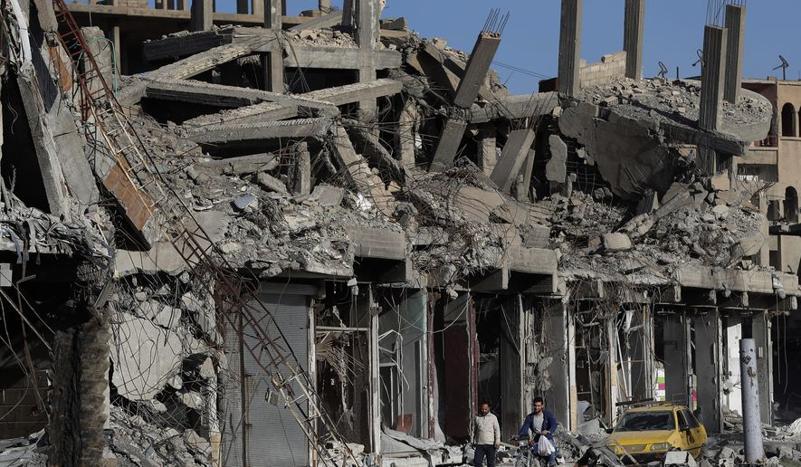 In this Thursday, April 5, 2018, photo, destroyed buildings line a street that was damaged during fighting between U.S.-backed Syrian Democratic Forces fighters and Islamic State militants, in Raqqa, Syria. (AP Photo/Hussein Malla) ** FILE **