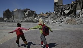 In this Thursday, April 5, 2018 photo, Syrian students run in front of buildings that were destroyed last summer during fighting between U.S.-backed Syrian Democratic Forces fighters and Islamic State militants, in Raqqa, Syria. Six months after IS was driven out, residents of Raqqa feel they have been abandoned as the world moves on. They are trying to rebuild but fear everyone around them: the Kurdish-led militia that administers the majority Arab city; Syrian government forces nearby; gangs who kidnap or rob whoever shows signs of having money; and IS militants who may still be hiding among the people. (AP Photo/Hussein Malla)