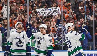 Vancouver Canucks' Henrik Sedin (33) and Daniel Sedin (22) acknowledge the crowd as it cheers for them during a break against the Edmonton Oilers in Edmonton, Alberta, Saturday, April 7, 2018. (Jason Franson/The Canadian Press via AP)