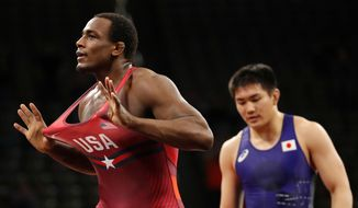 United States' J'den Cox, left, celebrates after defeating Japan's Takashi Ishiguro, right, in their 92 kg match in the Freestyle Wrestling World Cup, Saturday, April 7, 2018, in Iowa City, Iowa. (AP Photo/Charlie Neibergall)