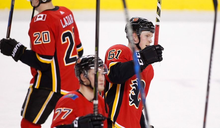 Calgary Flames players salute fans after defeating the Vegas Golden Knights 7-1 during an NHL hockey game Saturday, April 7, 2018, in Calgary, Alberta. (Larry MacDougal/The Canadian Press via AP)