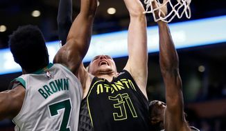 Boston Celtics' Jaylen Brown (7) battles Atlanta Hawks' Mike Muscala (31) for a rebound during the first quarter of an NBA basketball game in Boston, Sunday, April 8, 2018. (AP Photo/Michael Dwyer)