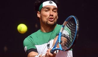 Italy's Fabio Fognini returns the ball to France's Lucas Pouille during a World Group Quarter final Davis Cup tennis match between Italy and France in Genoa, Italy, Sunday April 8, 2018. (Luca Zennaro/ANSA via AP)