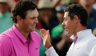 Patrick Reed, left, is congratulated by Rory McIlroy after winning the Masters golf tournament Sunday, April 8, 2018, in Augusta, Ga. (AP Photo/David Goldman)