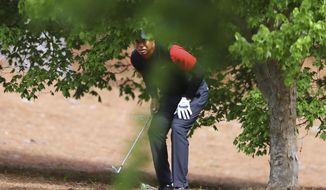 Tiger Woods prepares to hit out of the woods off the second fairway during his final round in the Masters at Augusta National Golf Club on Sunday, April 8, 2018, in Augusta, Ga. (Curtis Compton/Atlanta Journal-Constitution via AP)