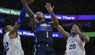 Dallas Mavericks' Dennis Smith Jr., center, shoots as Philadelphia 76ers' Richaun Holmes, left, and Markelle Fultz, right, defend during the first half of an NBA basketball game, Sunday, April 8, 2018, in Philadelphia. (AP Photo/Chris Szagola)