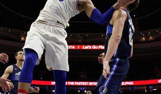 Philadelphia 76ers' Ben Simmons, left, of Australia, reacts after his dunk against Dallas Mavericks' Doug McDermott, right, during the first half of an NBA basketball game, Sunday, April 8, 2018, in Philadelphia. (AP Photo/Chris Szagola)