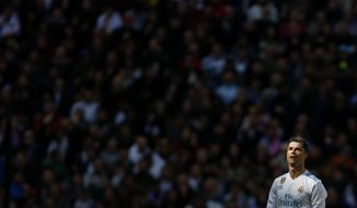 Real Madrid's Cristiano Ronaldo walks along the pitch after scoring a goal against Atletico Madrid during the Spanish La Liga soccer match between Real Madrid and Atletico Madrid at the Santiago Bernabeu stadium in Madrid, Sunday, April 8, 2018. Ronaldo scored once and the match ended in a 1-1 draw. (AP Photo/Francisco Seco)