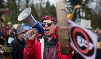 In this Saturday, April 7, 2018, photo, Cedar George-Parker addresses the crowd as protesters opposed to Kinder Morgan's plan on Trans Mountain pipeline extension, in Burnaby, British Columbia. Kinder Morgan is suspending all non-essential activities and related spending on the Trans Mountain pipeline expansion project. (Darryl Dyck/The Canadian Press via AP)