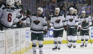 Minnesota Wild left wing Jason Zucker, in front of players at right, celebrates with teammates after scoring a goal against the San Jose Sharks during the second period of an NHL hockey game in San Jose, Calif., Saturday, April 7, 2018. (AP Photo/Jeff Chiu)