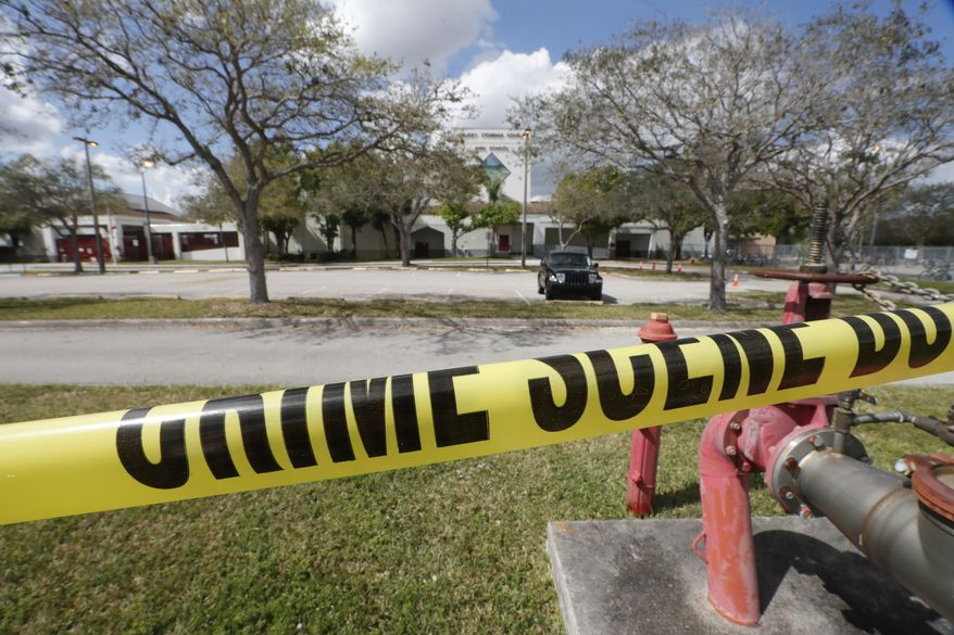 Crime scene tape runs outside Marjory Stoneman Douglas High School in Parkland, Fla., Sunday, Feb. 18, 2018. Authorities opened the streets around the school, which had been closed since a mass shooting on Wednesday. Nikolas Cruz, a former student, was charged with 17 counts of premeditated murder. (AP Photo/Gerald Herbert) ** FILE **