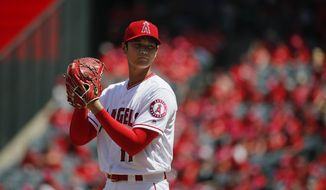 Los Angeles Angels starting pitcher Shohei Ohtani, of Japan, reads the sign while throwing against the Oakland Athletics during the first inning of a baseball game, Sunday, April 8, 2018, in Anaheim, Calif. (AP Photo/Jae C. Hong)