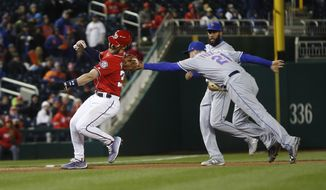 New York Mets third baseman Todd Frazier (21) tags Washington Nationals Bryce Harper (34) for the out during the seventh inning of baseball game, at Nationals Park, Monday, April 9, 2018 in Washington. Also on the field is New York Mets shortstop Amed Rosario (1). (AP Photo/Pablo Martinez Monsivais)