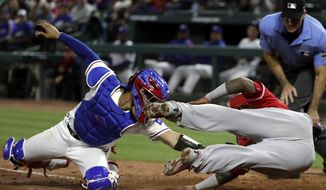 Texas Rangers catcher Robinson Chirinos, left, attempts to tag out Los Angeles Angels' Martin Maldonado, front right, who touches the bag with his hand as he dives into home in the sixth inning of a baseball game in Arlington, Texas, Monday, April 9, 2018. Home plate umpire Angel Hernandez, back right, watches the play. Hernandez ruled Maldonado out but after a video replay the call was reversed to say Maldonado was safe at the plate. (AP Photo/Tony Gutierrez)