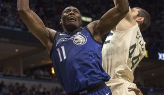 Orlando Magic center Bismack Biyombo, left, goes up for a basket against the defense of Milwaukee Bucks center Tyler Zeller, right, during the first half of an NBA basketball game Monday, April 9, 2018, in Milwaukee. (AP Photo/Darren Hauck)