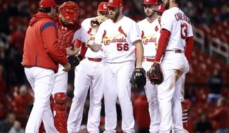 St. Louis Cardinals relief pitcher Greg Holland (56) is removed by manager Mike Matheny, left, during the 10th inning of a baseball game against the Milwaukee Brewers, Monday, April 9, 2018, in St. Louis. (AP Photo/Jeff Roberson)