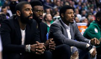 FILE - In this March 20, 2018, file photo, Boston Celtics guard Kyrie Irving, left, sit with teammates Jaylen Brown, center, and Marcus Smart during the first quarter of the team's NBA basketball game against the Oklahoma City Thunder, in Boston, Tuesday, March 20, 2018. The Celtics have had to overcome their share of adversity this season, battling injuries after an offseason overhaul that began with so much expectation. Offseason acquisitions Kyrie Irving and Gordon Hayward have both suffered season-ending injuries. Yet somehow Boston enters the playoffs as the No. 2 in the Eastern Conference with a legitimate chance to win the conference. (AP Photo/Charles Krupa, File)