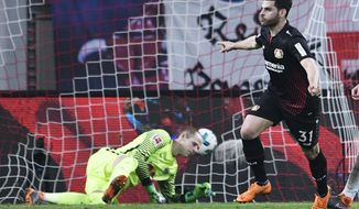 Leverkusen's Kevin Volland scores a goal during the German first division Bundesliga soccer match between RB Leipzig and Bayer Leverkusen in Leipzig, Germany, Monday, April 9, 2018. (AP Photo/Jens Meyer)