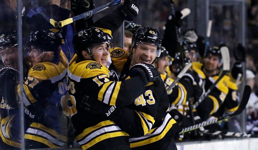 FILE - This March 19, 2018, file photo shows Boston Bruins forward Ryan Donato, left, being congratulated by Danton Heinen (43) after his first goal in his first NHL game, during the second period of a hockey game against the Columbus Blue Jackets in Boston. In the East, Boston suddenly looks like the team to beat, Pittsburgh has won the Stanley Cup two years in a row and awakened from a midseason funk and Tampa Bay has shown flashes of being unstoppable. (AP Photo/Charles Krupa, File) **FILE**