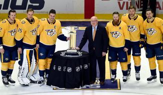 FILE - In this April 7, 2018, file photo, from left, Nashville Predators Ryan Johansen (92), Pekka Rinne (35), captain Roman Josi (59), National Hockey League Deputy Commissioner Bill Daly, Ryan Ellis (4), Mattias Ekholm (14), Filip Forsberg (9), stand next to the President's Trophy after accepting the trophy on behalf of the organization before an NHL hockey game against the Columbus Blue Jackets in Nashville, Tenn. The changing of the guard begins at the top, where Nashville clinched its first Central Division title by running away with the league's best record. (AP Photo/Mark Zaleski, File)