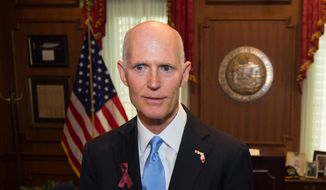 In this March 9, 2018, file photo, Florida Gov. Rick Scott talks to the media in his office after signing the Marjory Stoneman Douglas Public Safety Act at the Florida Capital in Tallahassee, Fla. (AP Photo/Mark Wallheiser, File)