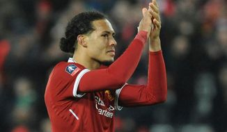 FILE - In this Friday, Jan. 5, 2018 file photo, Liverpool's Virgil van Dijk applauds fans after the final whistle of their English FA Cup Third Round soccer match against Everton at Anfield in Liverpool, England. Virgil van Dijk and Aymeric Laporte are the world's two most expensive defenders and signed at a combined cost of nearly $200 million in the January transfer window to take Liverpool and Manchester City to the next level. Van Dijk has stamped his authority immediately at Liverpool but fellow center back Laporte is still adapting to English soccer and hasn't managed to establish himself as first-choice pick at City. (AP Photo/Rui Vieira, file)