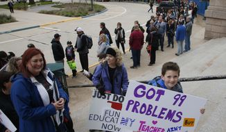 Six-year-old Coe Amos, a student in the Deer Creek school district of Edmond, Okla., stands in line to enter the state Capitol on the fifth day of protests over school funding, in Oklahoma City, Friday, April 6, 2018. (AP Photo/Sue Ogrocki)