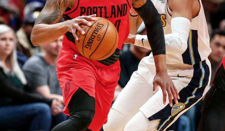 Portland Trail Blazers guard Damian Lillard, left, drives past Denver Nuggets guard Jamal Murray, right, during the first quarter of an NBA basketball game Monday, April 9, 2018, in Denver. (AP Photo/Jack Dempsey)