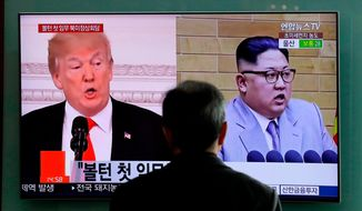 """FILE - In this March 27, 2018, file photo, a man watches a TV screen showing file footages of U.S. President Donald Trump, left, and North Korean leader Kim Jong Un during a news program at the Seoul Railway Station in Seoul, South Korea. A Trump administration official said Sunday, April 8, that the United States has now """"confirmed that Kim Jong Un is willing to discuss the denuclearization of the Korean Peninsula."""" The official wasn't authorized to be quoted by name and demanded anonymity. The meeting could occur as early as May. (AP Photo/Lee Jin-man, File)"""