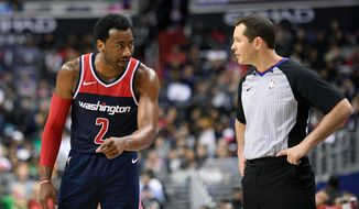 Washington Wizards guard John Wall (2) talks to referee Brian Forte, right, after he was called for a foul during the second half of the team's NBA basketball game against the Boston Celtics, Tuesday, April 10, 2018, in Washington. The Wizards won 113-101. (AP Photo/Nick Wass)
