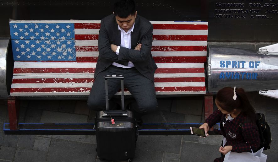 A woman walks by a man sitting outside an American apparel store at a shopping mall in Beijing, Tuesday, April 10, 2018. China's President Xi Jinping promised to cut auto import taxes, open China's markets further and improve conditions for foreign companies in a speech Tuesday that called for international cooperation against a backdrop of a spiraling dispute with Washington over trade and technology. (AP Photo/Andy Wong)