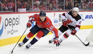 Washington Capitals left wing Andre Burakovsky (65) skates with the puck against New Jersey Devils defenseman John Moore (2) during the second period of an NHL hockey game, Saturday, April 7, 2018, in Washington. (AP Photo/Nick Wass) ** FILE **