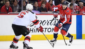 Washington Capitals left wing Jakub Vrana (13) skates with the puck against New Jersey Devils defenseman Andy Greene (6) during the second period of an NHL hockey game, Saturday, April 7, 2018, in Washington. (AP Photo/Nick Wass) ** FILE **