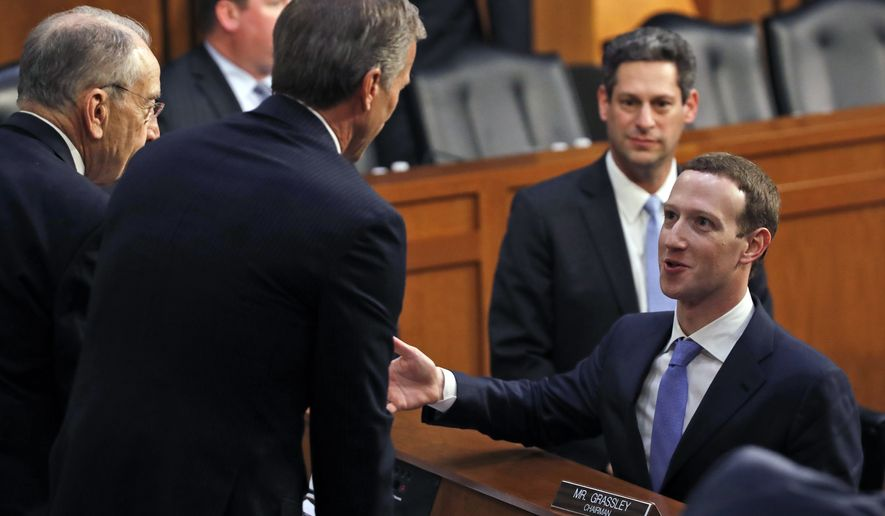 Senate Judiciary Committee Chairman Chuck Grassley, Iowa Republican (left) and Commerce Committee Chairman John Thune, South Dakota Republican, speak with Facebook CEO Mark Zuckerberg after a joint hearing of the Commerce and Judiciary Committees on Tuesday about the use of Facebook data to target American voters in the 2016 election. (Associated Press)