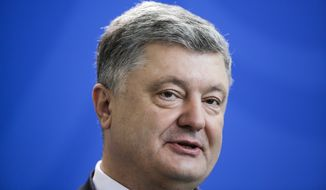 The President of Ukraine, Petro Poroshenko, briefs the media during a news conference with German Chancellor Angela Merkel after a meeting at the chancellery in Berlin, Germany, Tuesday, April 10, 2018. (AP Photo/Markus Schreiber)