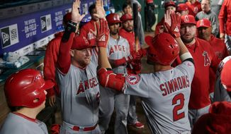 Los Angeles Angels' Andrelton Simmons (2) celebrates with teammates after hitting a home run during the third inning of a baseball game against the Texas Rangers in Arlington, Texas, Tuesday, April 10, 2018. (AP Photo/Cooper Neill)