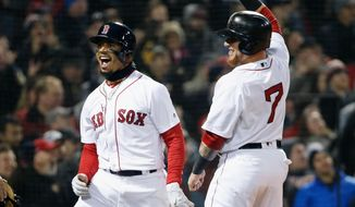Boston Red Sox's Mookie Betts, left, celebrates with Christian Vazquez (7) after scoring on a triple by Andrew Benintendi during the second inning of a baseball game against the New York Yankees in Boston, Tuesday, April 10, 2018. (AP Photo/Michael Dwyer)