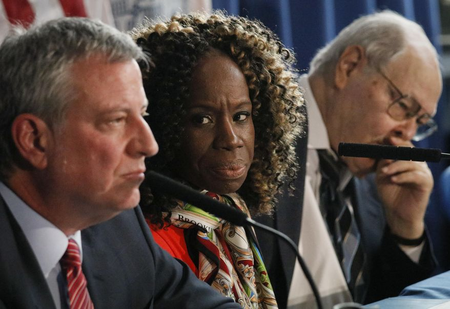 CORRECTS SPELLING OF LAST NAME TO BREZENOFF, NOT BEZENOFF - Outgoing New York City Housing Authority (NYCHA) chair Shola Olatoye, center, and interim NYCHA chair Stanley Brezenoff, right, listen as New York Mayor Bill de Blasio speaks during a press conference during his visit to NYCHA's Ocean Bay Bayside Apartments, Tuesday April 10, 2018, in the Arverne section of the Queens borough of New York. (AP Photo/Bebeto Matthews)