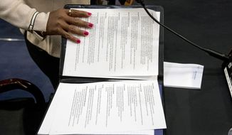An aide to Facebook CEO Mark Zuckerberg closes a binder of notes left on the table as Zuckerberg takes a short break from testifying before a joint hearing of the Commerce and Judiciary Committees on Capitol Hill in Washington, Tuesday, April 10, 2018, about the use of Facebook data to target American voters in the 2016 election. (AP Photo/Andrew Harnik)