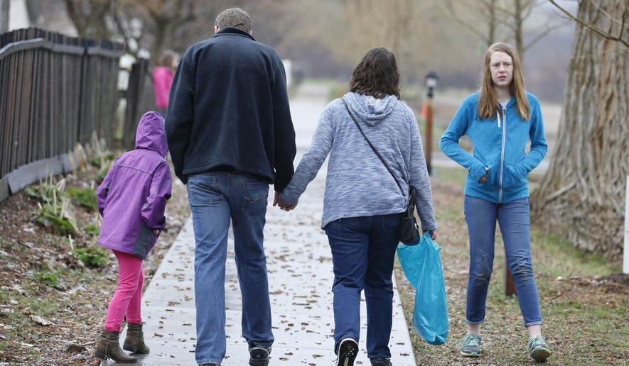 In this April 6, 2018, photo, Amy Coulter, center right, and her husband Mark walk together with their children April, 7, left, and Kendra, 12, at the Place Heritage Park in Salt Lake City. After Utah passed the country's first law legalizing so-called free-range parenting, groups from New York to Texas are pushing for similar steps to bolster the idea that supporters say is an antidote for anxiety-plagued parents and overscheduled children. Amy Coulter, a stay-at-home Utah mother, said she doesn't call herself a free-range parent. But she does avoid intervening with teachers on her older children's grades and encourages her children to use their own money to buy things at the grocery store. (AP Photo/Rick Bowmer)