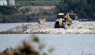 FILE - In this Sept. 13, 2017, file photo, workers are shown at San Jacinto River Waste Pits near the Interstate 10 bridge over the river in Channelview, Texas. Federal environmental regulators have reached a long-awaited agreement with the owners of a polluted toxic waste site in Texas that was damaged during Hurricane Harvey, releasing dangerous chemicals into a river. The Environmental Protection Agency says it reached agreement with International Paper Co. and McGinnes Industrial Maintenance Corp. to design a plan to remove dioxin-contaminated materials from the San Jacinto River Waste Pits Superfund site. (AP Photo/David J. Phillip, File)