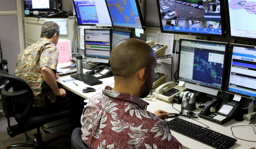 "FILE - In this Dec. 1, 2017 file photo, Hawaii Emergency Management Agency officials work at the department's command center in Honolulu. The missile alert Hawaii mistakenly sent to the public has promoted the Federal Communications Commission to recommend government workers avoid using the phrase ""this is not a drill"" during practice sending emergency notices. The FCC included the advice Tuesday, April 10, 2018, in its final report on what went wrong when Hawaii in January accidentally warned a ballistic missile was about to hit the islands. (AP Photo/Caleb Jones, File)"