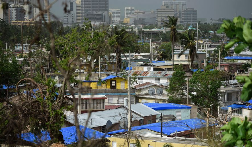 In this Oct. 19, 2017, file photo, homes stand covered with FEMA tarps in the Cantera area, as the banking zone stands in the background in San Juan, Puerto Rico. (AP Photo/Carlos Giusti, File)