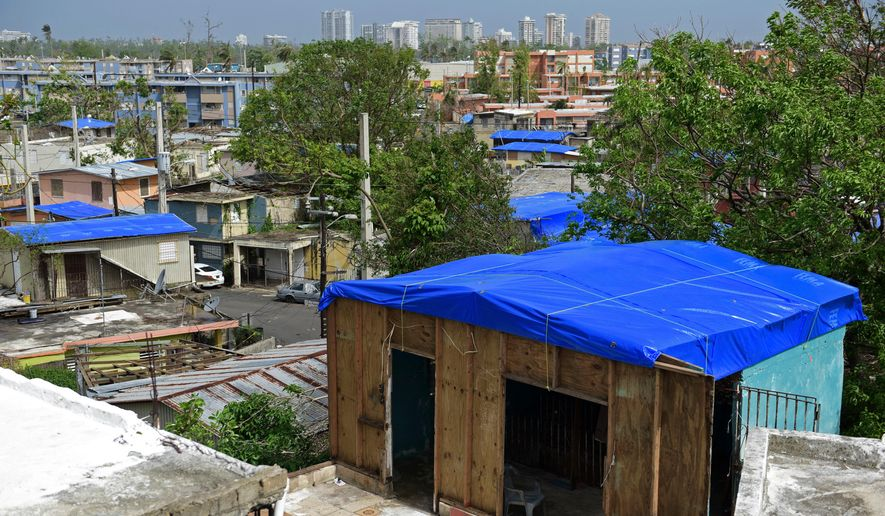 In this Oct. 19, 2017, file photo, homes in the Cantera area are covered with FEMA tarps, where buildings from the Hato Rey area stand in the background in San Juan, Puerto Rico. The Federal Emergency Management Agency awarded contracts to deliver hurricane supplies without adequately researching whether winning bidders could deliver what they promised, according to a new investigation by Democrats on a Senate oversight committee. (AP Photo/Carlos Giusti, File)