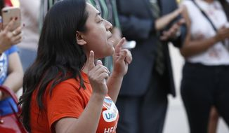 Karina Ruiz, of the Arizona Dream Act Coalition, shouts in protest of the Arizona Supreme Court ruling against young immigrants granted deferred deportation status under the 2012 Deferred Action for Childhood Arrivals program, during a demonstration at the Arizona Capitol in Phoenix on Monday, April 9, 2018. Immigrants under the program are not eligible for lower in-state college tuition, the supreme court ruled Monday. (AP Photo/Ross D. Franklin)