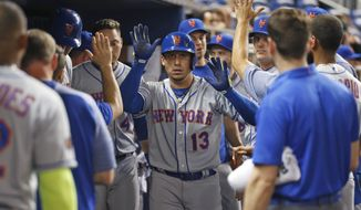 New York Mets' Asdrubal Cabrera (13) celebrates with teammates after hitting a home run during the fourth inning of a baseball game against the Miami Marlins, Tuesday, April 10, 2018, in Miami. (AP Photo/Wilfredo Lee)
