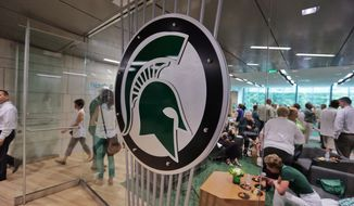 FILE - In this Aug. 25, 2014, file photo, people tour the new North End Zone Complex renovations at Spartan Stadium on the Michigan State Campus in East Lansing, Mich. A woman who attends Michigan State University filed a federal lawsuit against the school Monday, April 9, 2018, alleging that three former men's basketball players sexually assaulted her at an off-campus apartment in 2015 and that she was discouraged from reporting what happened. (Ryan Garza/Detroit Free Press via AP, File)
